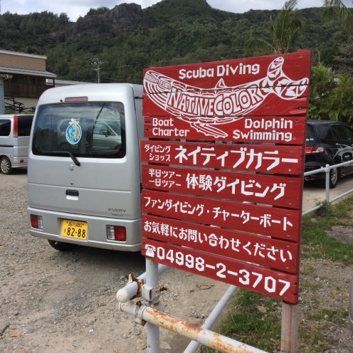One of Pelan Village's vans in a parking lot near the grocery store. Red chickens roam freely about. Since Ogasawara is a touristic hotspot, signs advertising oceanic recreation activities are prominent on the street.