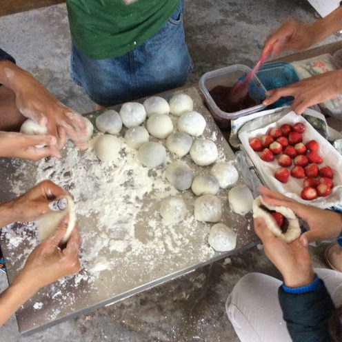 Making special festive mochi filled with a generous scoop of red bean paste and a single plump strawberry, and then dusted with some rice flour.