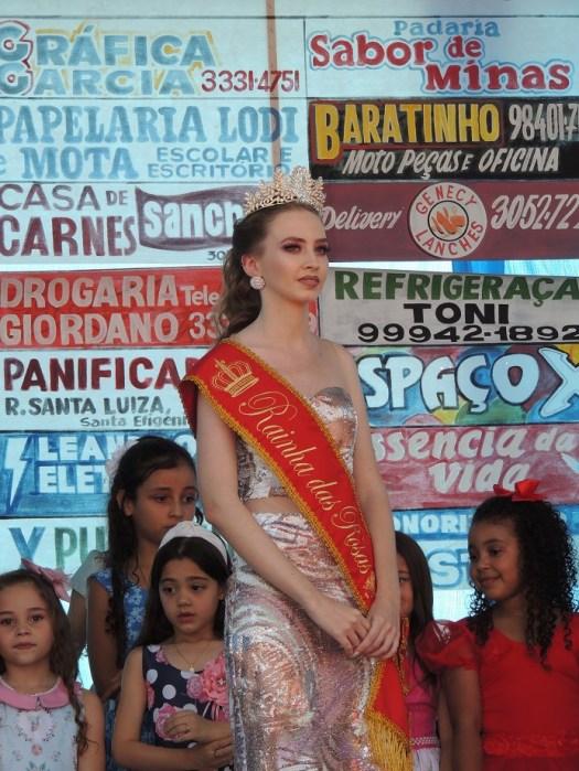 Rainha no palco ao lado das meninas.