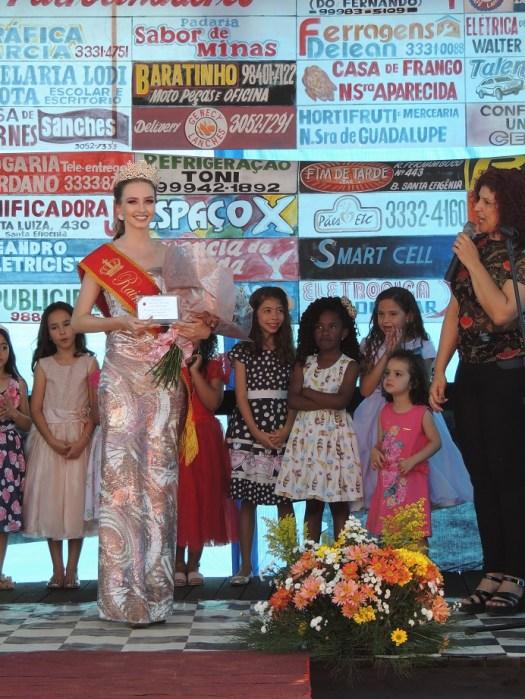 Com buquê e placa no palco sendo observada pelas crianças.