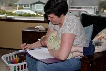 Baby M nursing while mom writes notes in her Reiki binder.  Multi tasking is not new to moms.