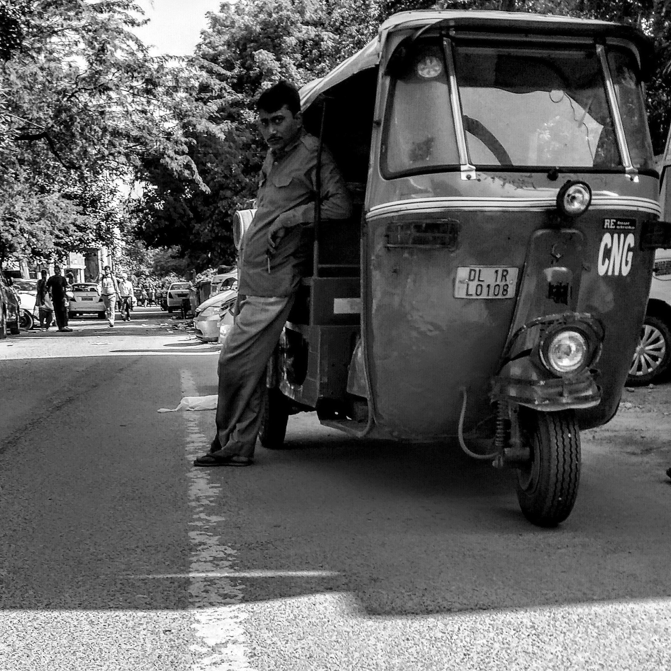 An auto-rickshaw driver waits outside Gulmohar Park, an affluent, upmarket and green neighbourhood in South Delhi.