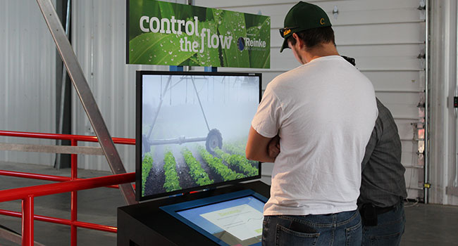 Man in front of a large display watching a movie about watering farmland.