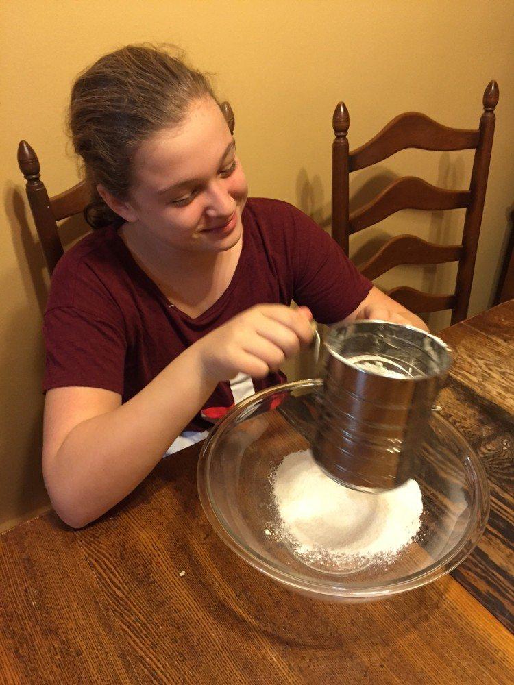 Girl sifting flour