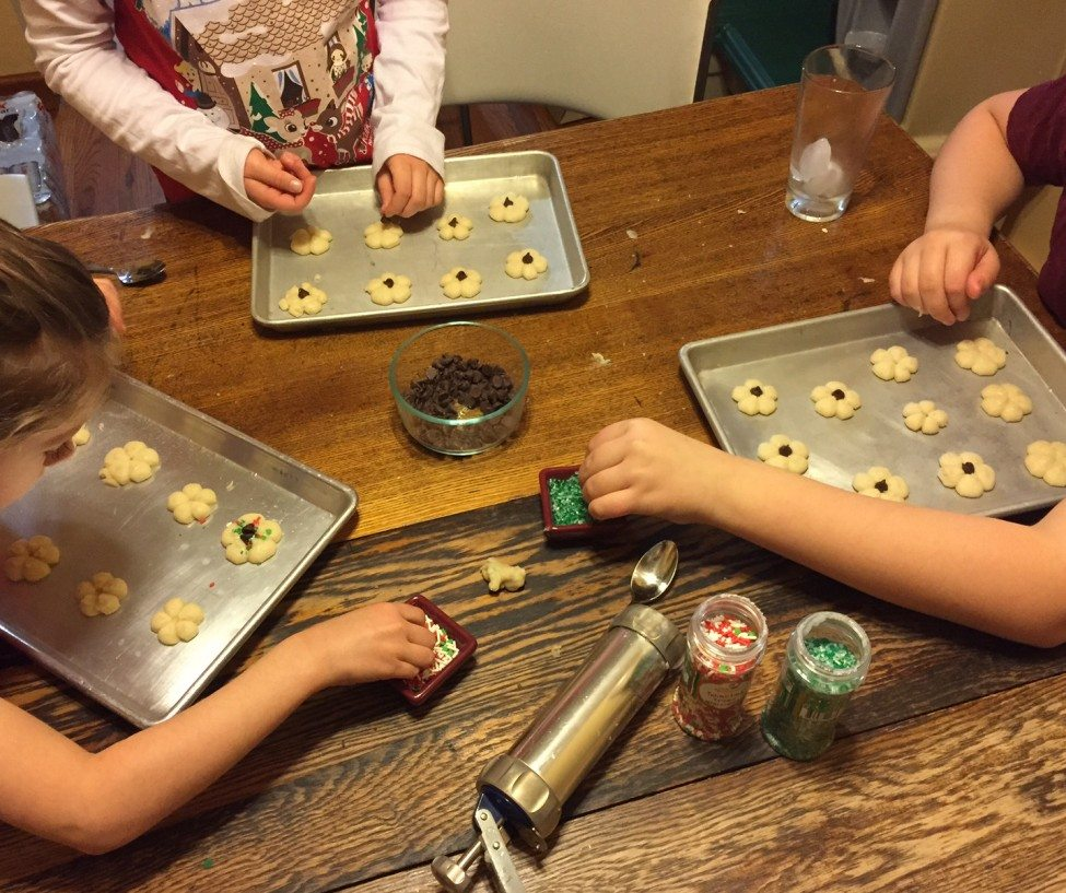 Three children decorating butter cookies on the table