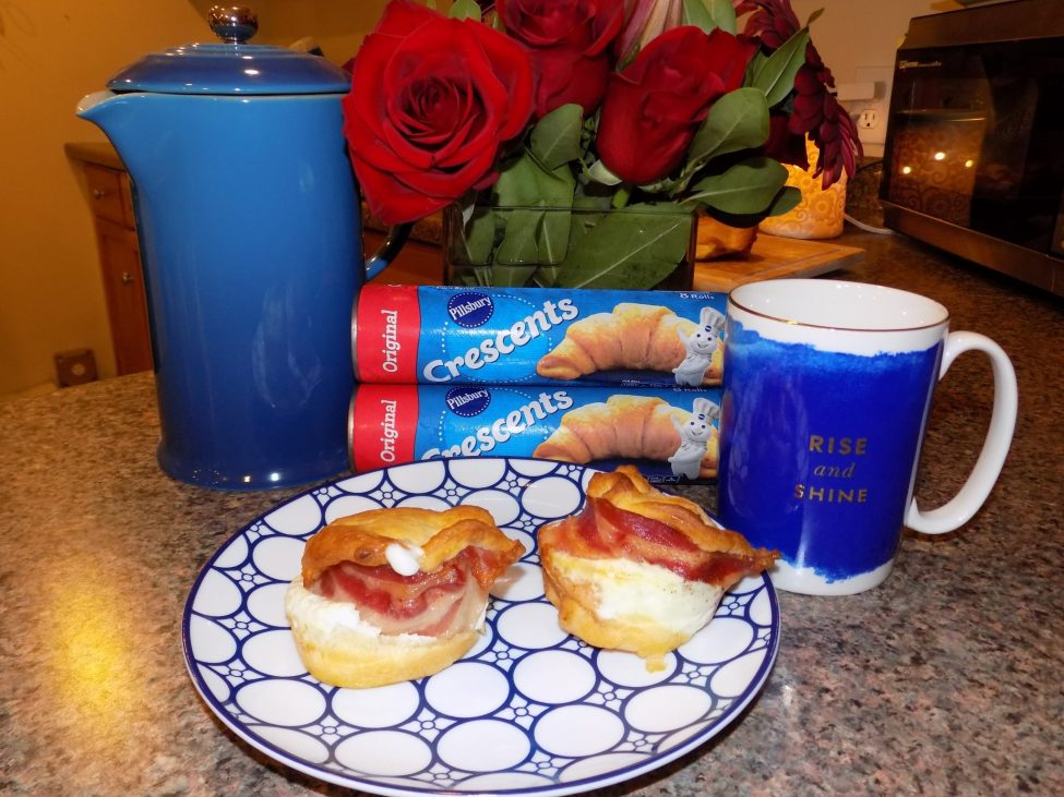 Two breakfast sandwiches on plate with crescent roll packages in background.