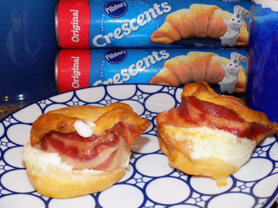 Two breakfast sandwich scramblers on plate with crescent roll packages in background.