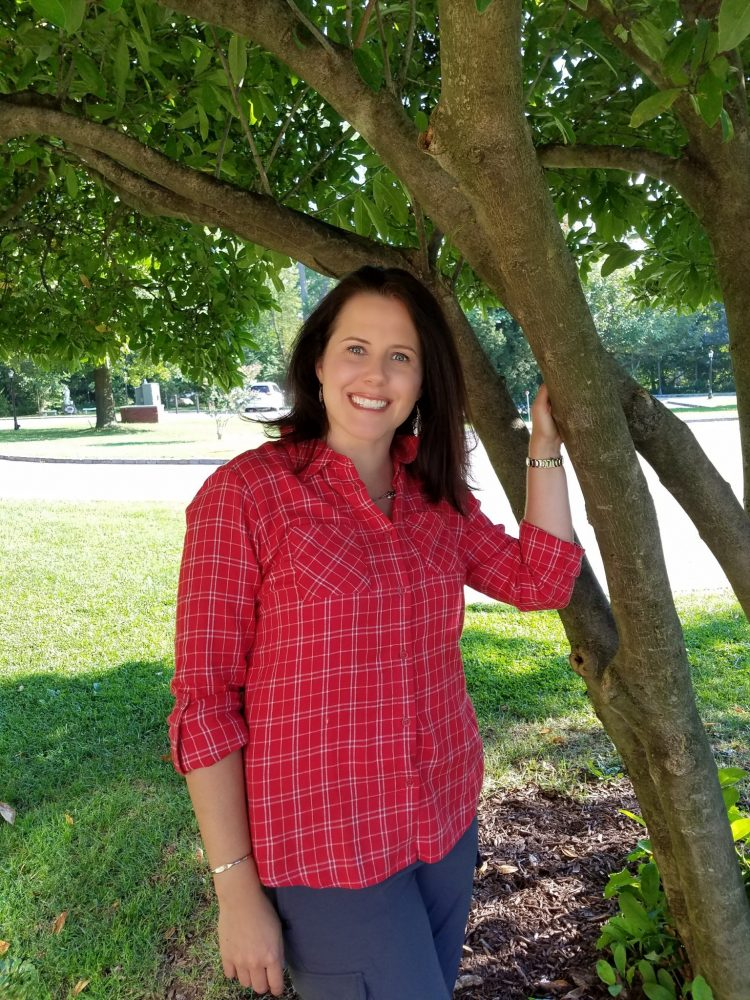 Woman in red shirt standing under tree