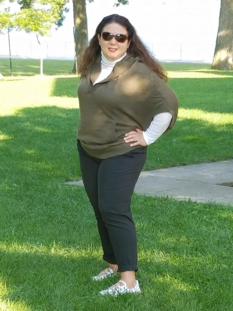 woman wearing green hoodie over white long sleeve shirt with dark green pants