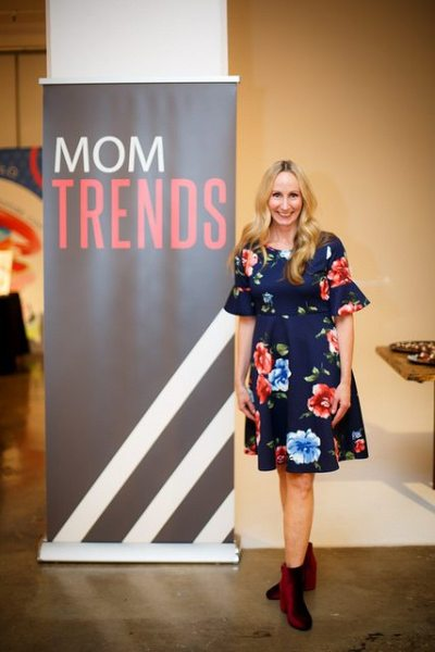 Woman in floral print dress beside Mom Trends banner