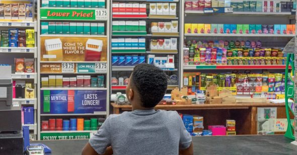 Boy looking standing at a convenience store counter and looking at cigarettes on the wall.