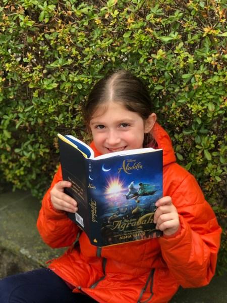 Girl holding Aladdin Far From Agrabah book.