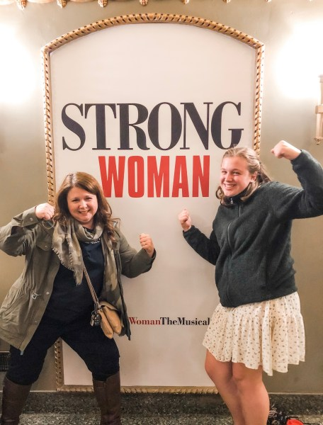Two women flex posing in front of Pretty Woman the Musical sign.