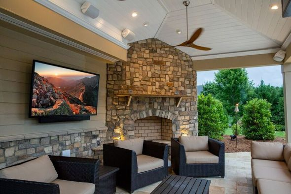 Outdoor TV mounted on the wall of an outdoor deck.