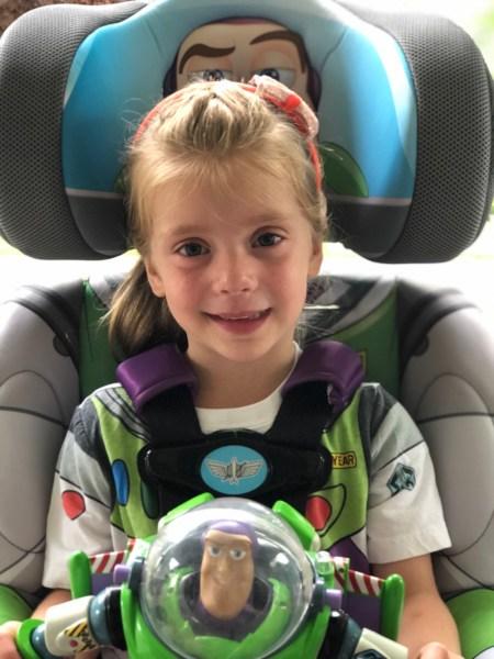 Girl sitting in Buzz Lightyear KidsEmbrace booster seat.