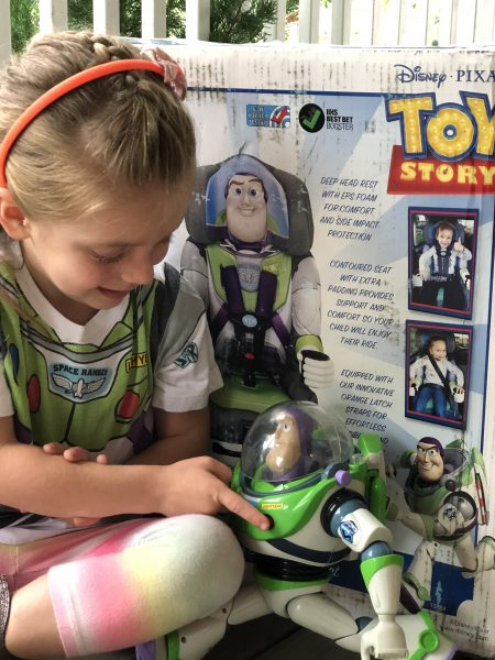 Girl with Buzz Lightyear toy sitting in front of booster seat box.