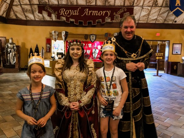 Two girls posing with the Queen at Medieval Times.