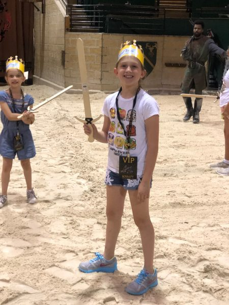 Two girls holding wood swords at Medieval Times.