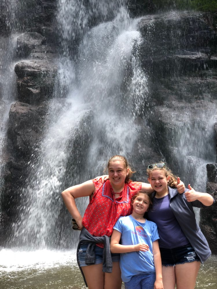 Three girls standing in front of a waterfall.