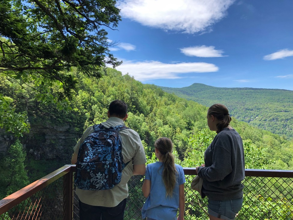 Man and two girls looking at the Great Northern Catskills from an observation deck.