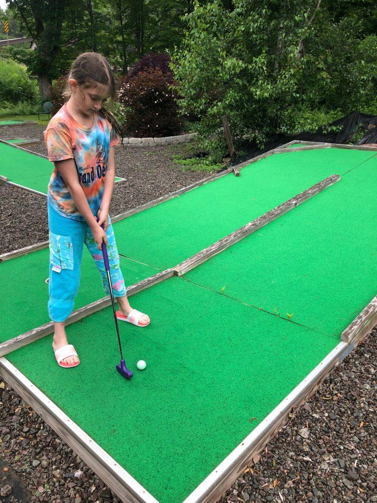 Girl playing mini-golf.