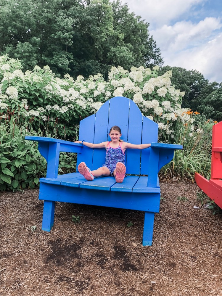 Girl sitting on giant blue chair.