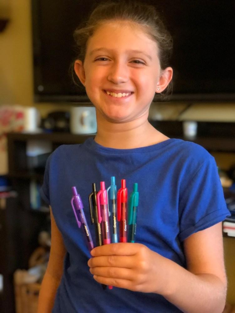 Girl holding Crayola Take Note! gel pens.
