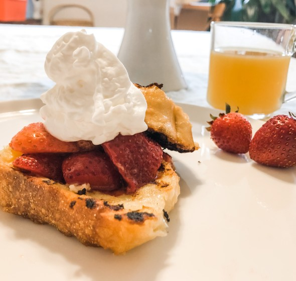 French toast topped with whipped cream on plate