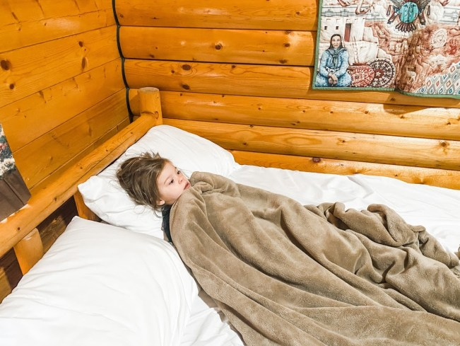 Toddler cozied up in mom and dad's bed
