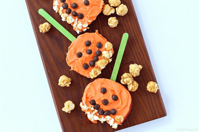 Pumpkin apple pops Need a festive fall snack that kids love? Try these Pumpkin Apple Pops for a fun Jack-O-Lantern inspired snack, featuring G.H. Cretors Popcorn #Snack #Halloween #Recipe