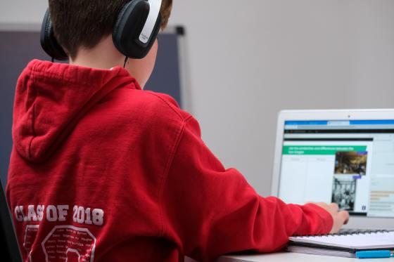 Zdjęcie przedstawiające dziecko siedzące przed laptopem