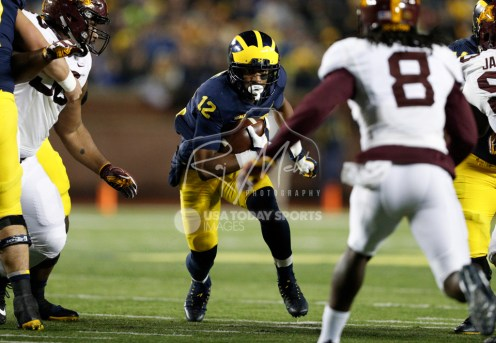 Nov 4, 2017; Ann Arbor, MI, USA; Michigan Wolverines running back Chris Evans (12) runs the ball toward Minnesota Golden Gophers defensive back Duke McGhee (8) during the first quarter at Michigan Stadium. Mandatory Credit: Raj Mehta-USA TODAY Sports
