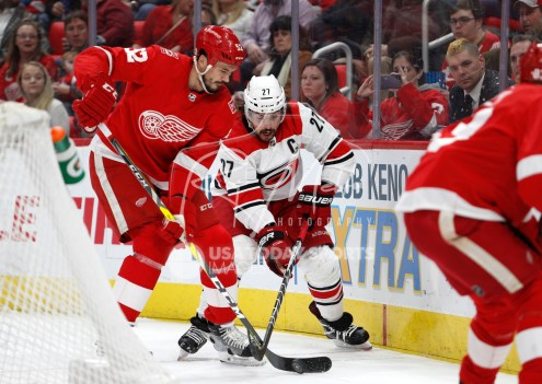 Feb 24, 2018; Detroit, MI, USA; Carolina Hurricanes defenseman Justin Faulk (27) and Detroit Red Wings defenseman Jonathan Ericsson (52) fight for the puck during the first period at Little Caesars Arena. Mandatory Credit: Raj Mehta-USA TODAY Sports