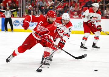 Feb 24, 2018; Detroit, MI, USA; Detroit Red Wings center Henrik Zetterberg (40) gets defended by Carolina Hurricanes defenseman Trevor van Riemsdyk (57) during the second period at Little Caesars Arena. Mandatory Credit: Raj Mehta-USA TODAY Sports