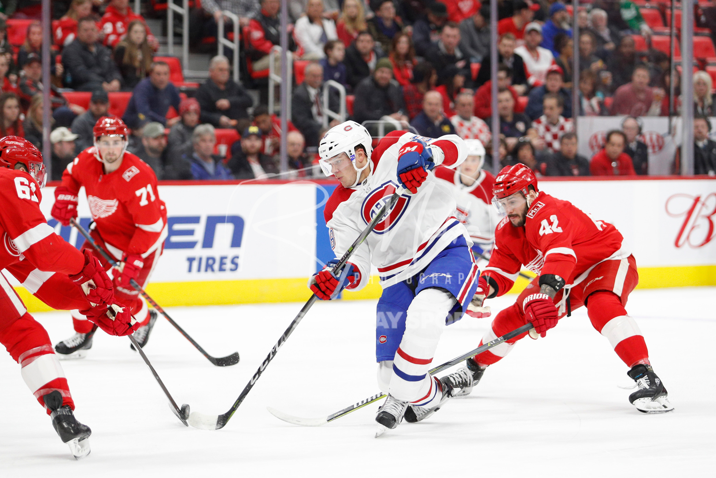 Apr 5, 2018; Detroit, MI, USA; Montreal Canadiens defenseman Noah Juulsen (58) gets defended by Detroit Red Wings defenseman Xavier Ouellet (61) and right wing Martin Frk (42) during the first period at Little Caesars Arena. Mandatory Credit: Raj Mehta-USA TODAY Sports