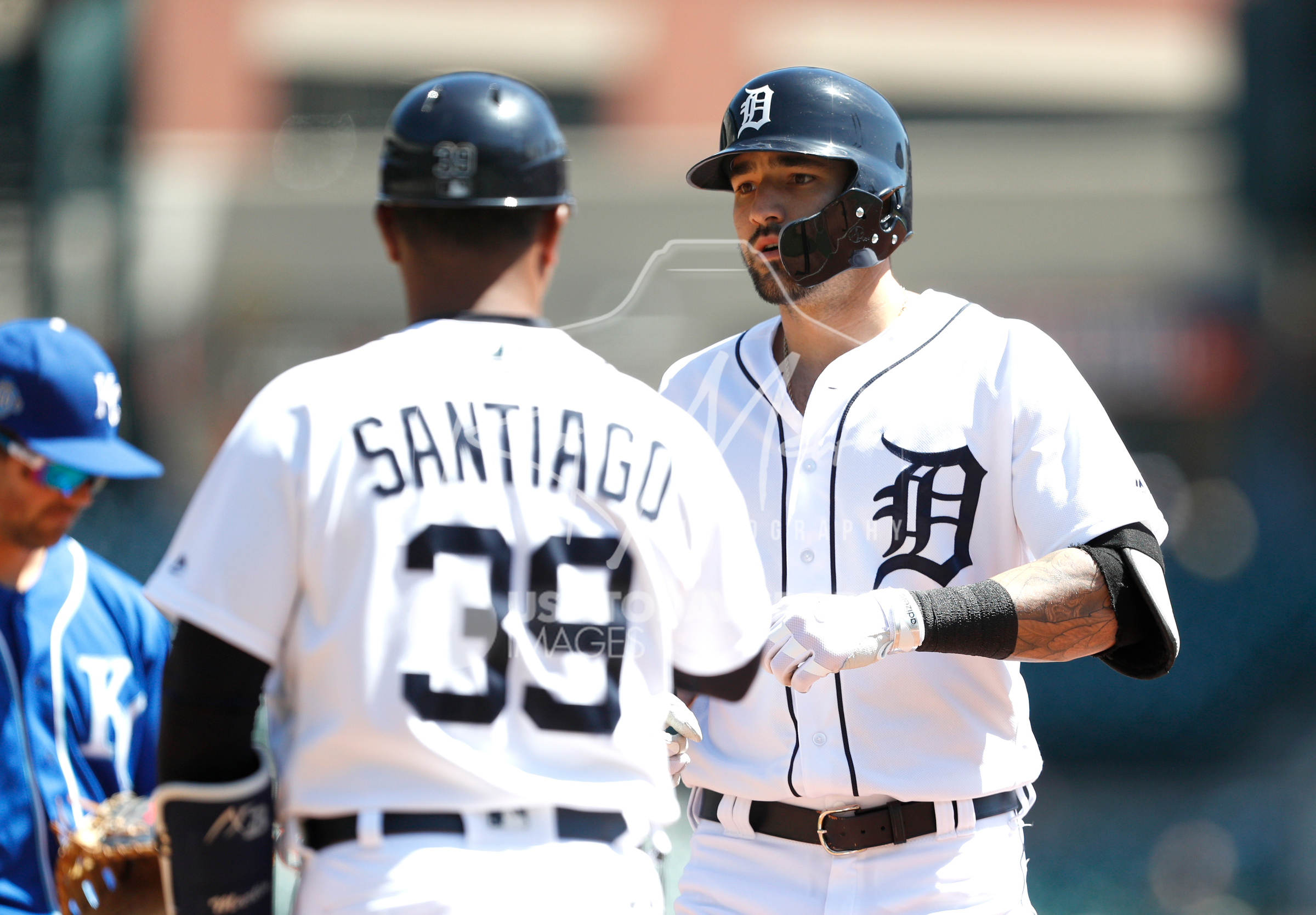 Apr 22, 2018; Detroit, MI, USA; Detroit Tigers right fielder Nicholas Castellanos (9) stands next to first base coach Ramon Santiago (39) after getting a hit for a single during the first inning against the Kansas City Royals at Comerica Park. Mandatory Credit: Raj Mehta-USA TODAY Sports