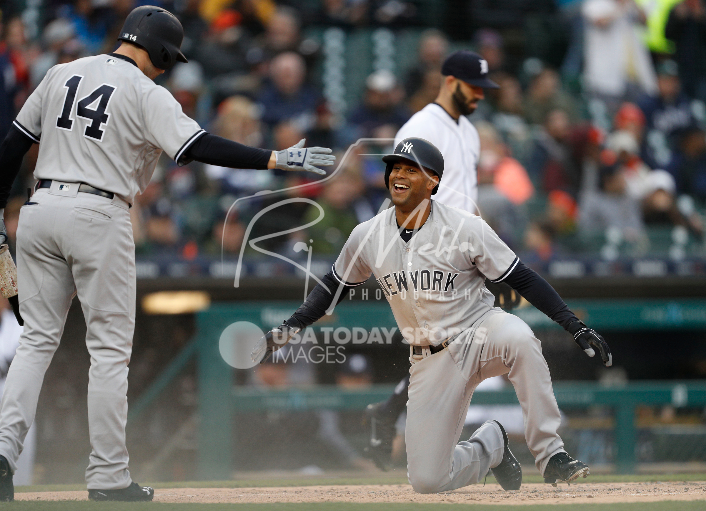 Apr 13, 2018; Detroit, MI, USA; New York Yankees center fielder Aaron Hicks (31) gets up to celebrate with second baseman Neil Walker (14) after sliding for a two run inside the park home run during the second inning against the Detroit Tigers at Comerica Park. Mandatory Credit: Raj Mehta-USA TODAY Sports