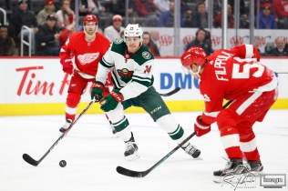 Feb 27, 2020; Detroit, Michigan, USA; Minnesota Wild center Joel Eriksson Ek (14) gets the loose puck against Detroit Red Wings center Valtteri Filppula (51) during the first period at Little Caesars Arena. Mandatory Credit: Raj Mehta-USA TODAY Sports