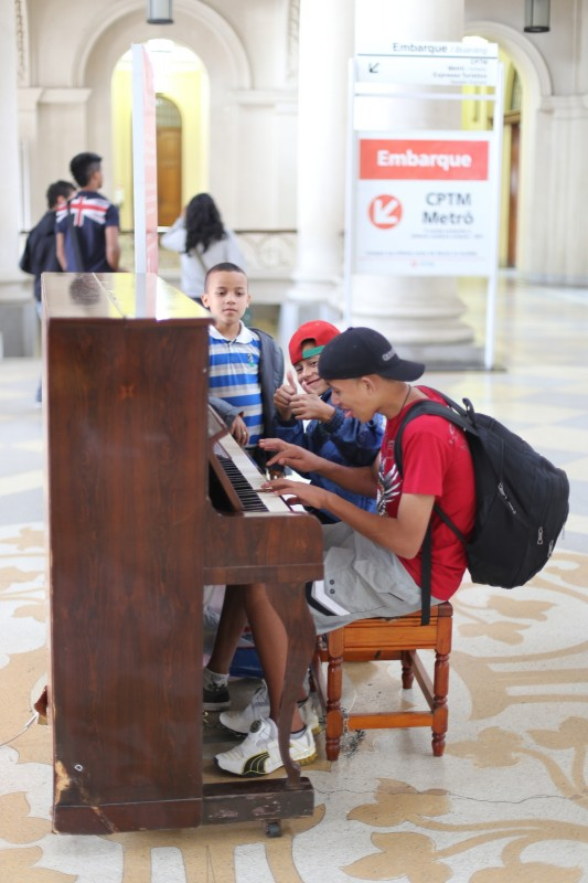 Some boys on the piano at the subway + train station.