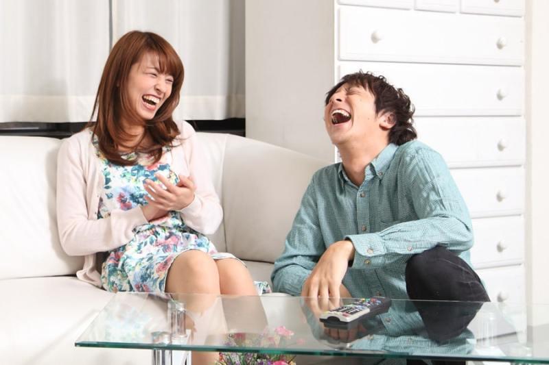 部屋で大笑いをしているカップル