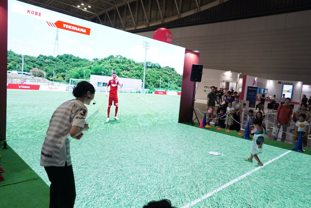A young footballer passes the ball to Vissel Kobe star David Villa at a customized augmented reality booth.