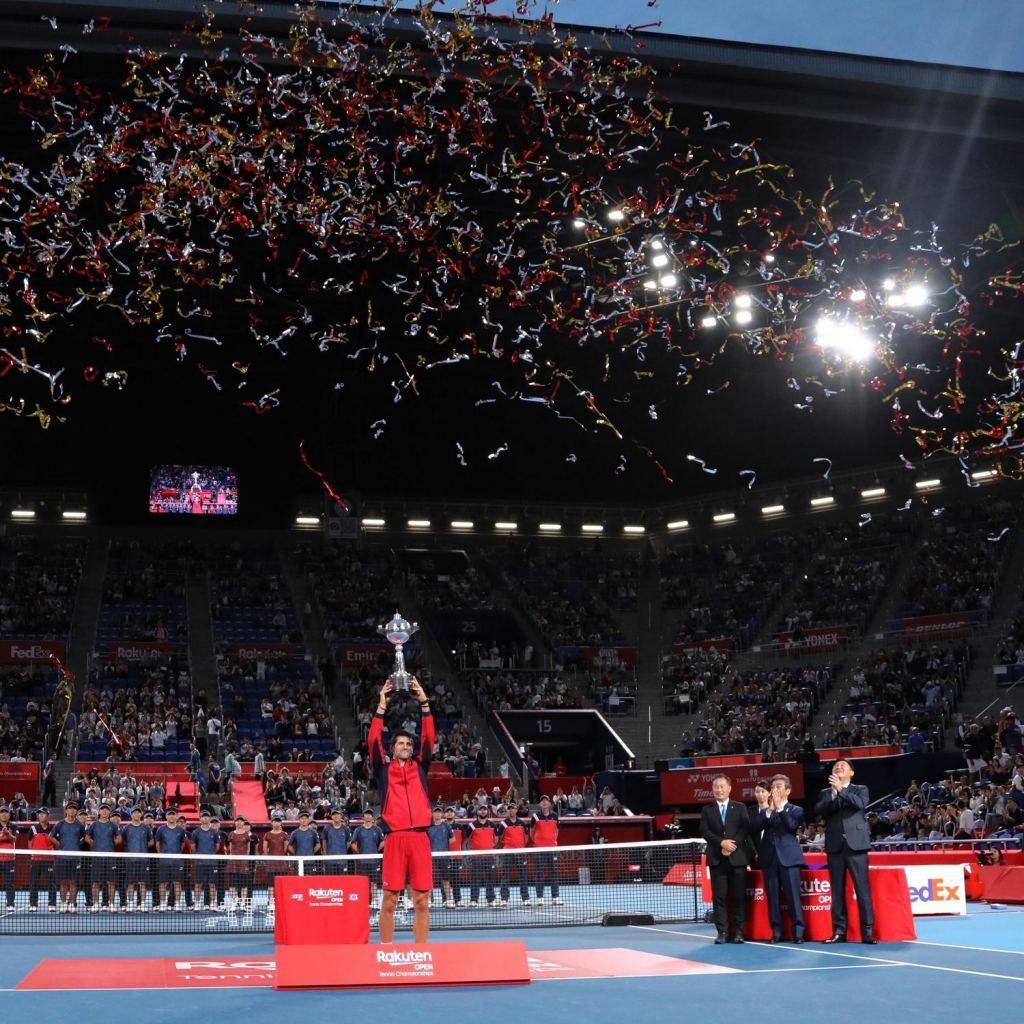 Djokovic holds the Rakuten Open trophy high following his final triumph.