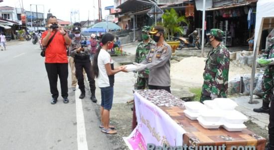 TNI dan POLRI di Nias Selatan saat membagikan nasi kotak dan masker kepada warga. Foto: Rakyatsumut.com/ Saksikan Sarumaha