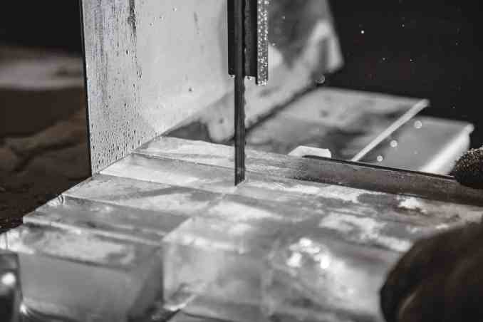 A bandsaw cuts the 300-lb. block of ice into cubes for cocktails.