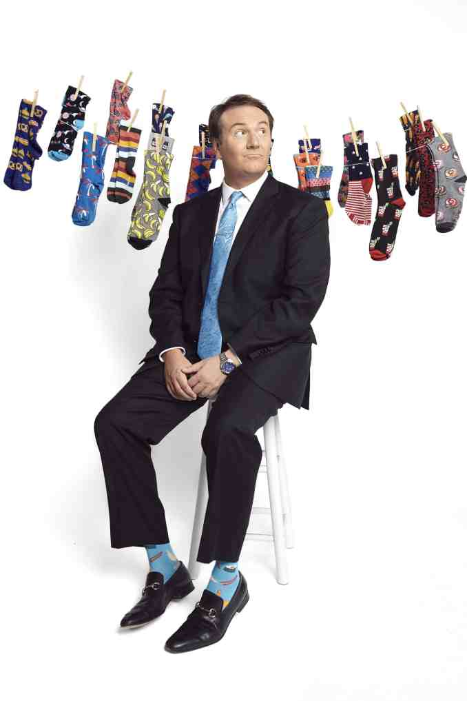 Local news anchor, Bill Young, posing with his sock collection