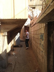 Mohamad walking through narrow alleys that are inaccessible to wheelchairs