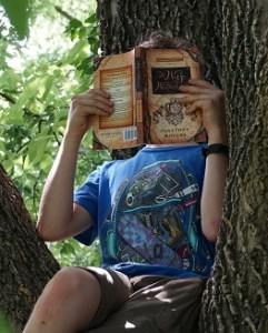 Child reading The Wilderking Trilogy: The Way of the Wilderking