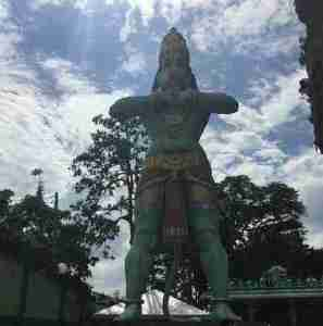 Large statue of a green monkey at entrance batu caves