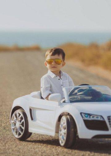 kid looking elegant in his electric car