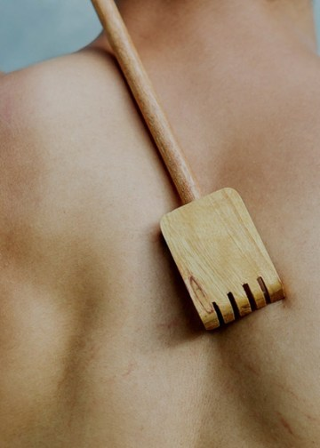 man scratching his back with a wooden scratcher